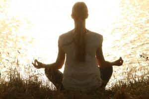 Девушка медитирует у озера